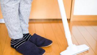 床を掃除機がけする一人暮らしの女性